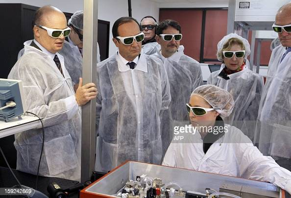 French President Francois Hollande wearing security glasses looks at a technician at work as he visits the Amplitude Systemes plant specialized in...