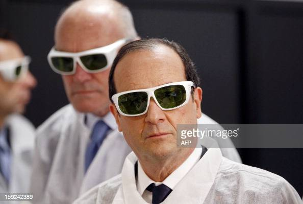 French President Francois Hollande wearing security glasses looks on as he visits the Amplitude Systemes plant specialized in ultrafast diodepumped...