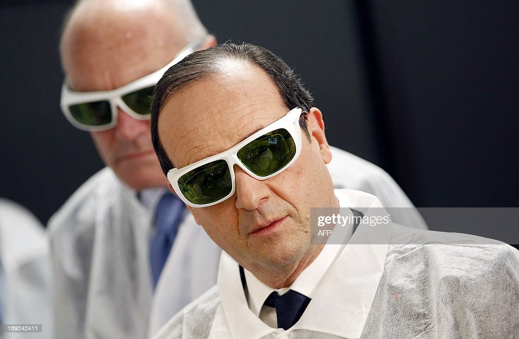 French President Francois Hollande wearing security glasses looks on as he visits the Amplitude Systemes plant, specialized in ultrafast diode-pumped solid-state lasers, in Pessac near Bordeaux, in southwestern France, on January 10, 2013.