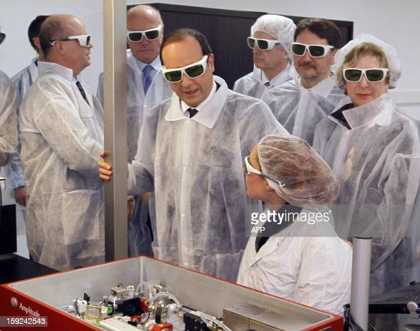 French President Francois Hollande wearing security glasses talks to a technician as he visits the Amplitude Systemes plant specialized in ultrafast...