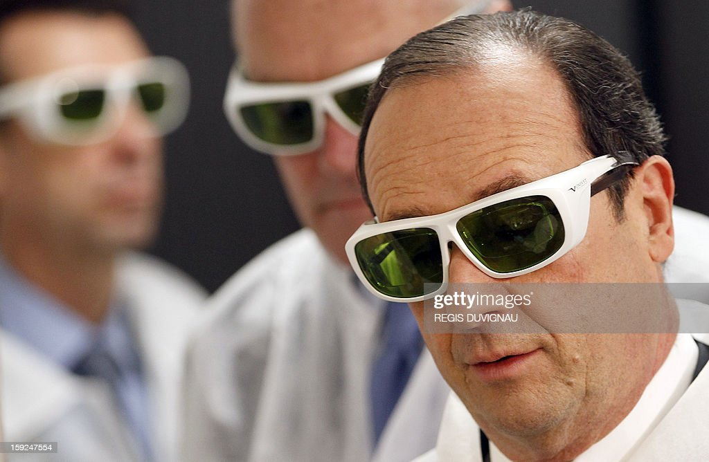 French President Francois Hollande wears protective glasses as he visits Amplitude Systemes manufacture in Pessac near Bordeaux, southwestern France, on January 10, 2013. Hollande was in the region for a visit dedicated to future investments and high-tech companies. POOL