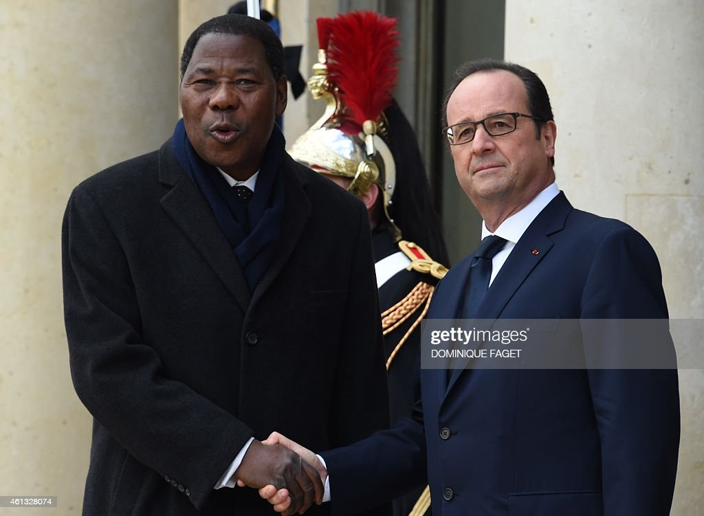 French President Francois Hollande (R) welcomes Benin's President Thomas Boni Yayi (C) at the Elysee Palace before attending a Unity rally Marche Republicaine on January 11, 2015 in Paris in tribute to the 17 victims of a three-day killing spree by homegrown Islamists. The killings began on January 7 with an assault on the Charlie Hebdo satirical magazine in Paris that saw two brothers massacre 12 people including some of the country's best-known cartoonists, the killing of a policewoman and the storming of a Jewish supermarket on the eastern fringes of the capital which killed 4 local residents. AFP PHOTO / DOMINIQUE FAGET