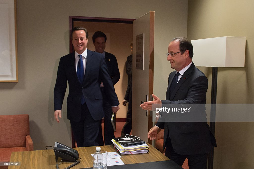 French President Francois Hollande (R) welcomes British Prime Minister David Cameron (L) and Dutch Prime Minister Mark Rutte (C) prior to take part in a meeting at the EU Headquarters, on November 23, 2012 in Brussels, as part of a two-day European Union leaders summit called to agree a hotly-contested trillion-euro budget through 2020. European leaders voiced pessimism on reaching a deal on a trillion-euro EU bdget, as gruelling talks pushed into a second day with little prospect of bridging bitter divisions. POOL AFP PHOTO / BERTRAND LANGLOIS