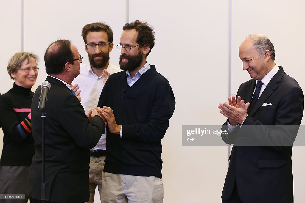 French President Francois Hollande (L) welcomes former hostages Tanguy Moulin-Fournier (C) and his brother Cyril Moulin-Fournier (3rdL) arriving from Yaounde, on April 20, 2013 at the Orly airport near Paris. The French members of the Moulin-Fournier family were released after being held in Nigeria for two months by an al-Qaeda-linked Islamist group called Boko Haram and left Cameroon for France on April 19, 2013 accompanied by French Foreign Minister Laurent Fabius (R).