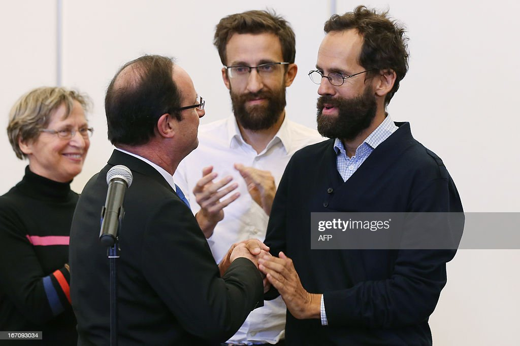 French President Francois Hollande (L) welcomes former hostages Tanguy Moulin-Fournier (R) and his brother Cyril Moulin-Fournier (C) arriving from Yaounde, on April 20, 2013 at the Orly airport near Paris. The French members of the Moulin-Fournier family were released after being held in Nigeria for two months by an al-Qaeda-linked Islamist group called Boko Haram and left Cameroon for France on April 19, 2013 accompanied by French Foreign Minister Laurent Fabius.