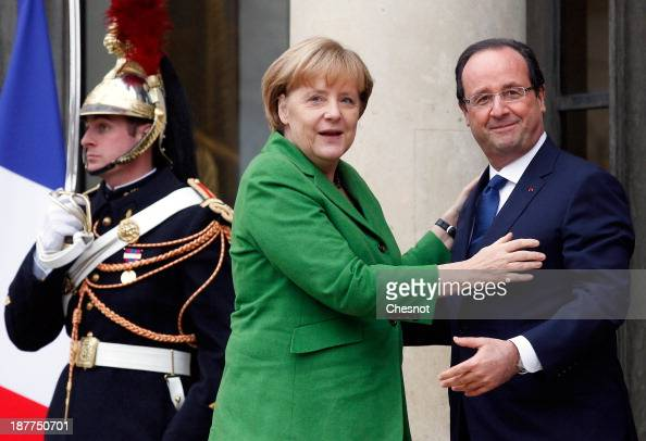 French President Francois Hollande welcomes German chancellor Angela Merkel prior to their meeting at the Elysee Palace on November 12 2013 in Paris...