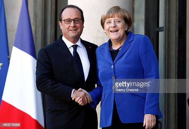French President Francois Hollande welcomes German Chancellor Angela Merkel prior to their meeting at the Elysee Presidential Palace on October 02...