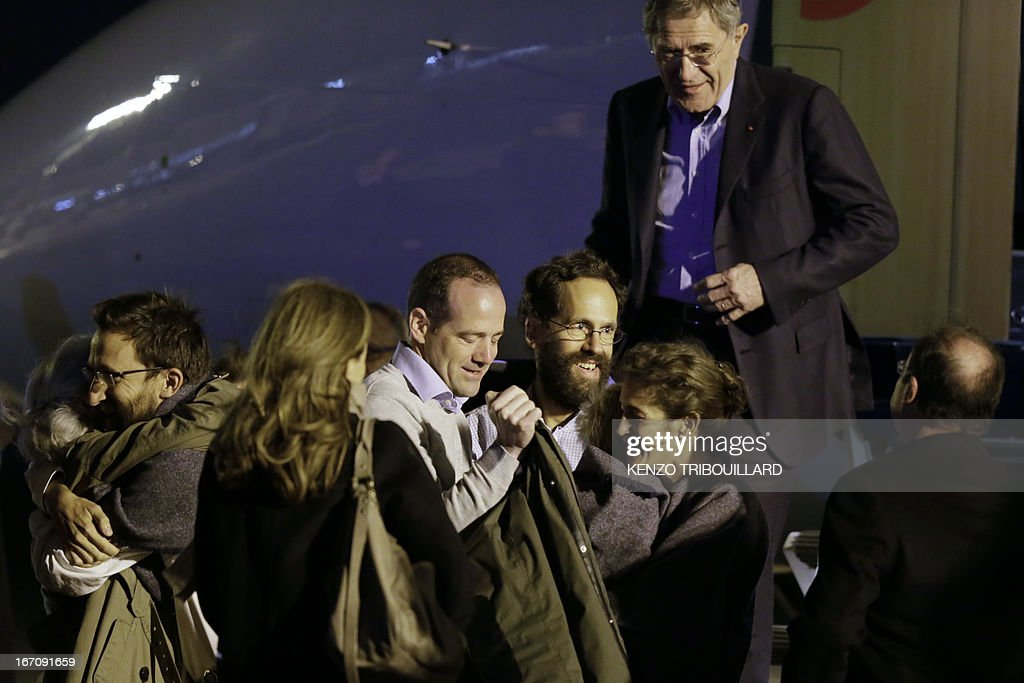 French President Francois Hollande (R) welcomes members of the Moulin-Fournier family as they arrive from Yaounde, at the Orly airport, near Paris, on April 20, 2013. A family of seven including four children who were held for two months by Islamists in Nigeria flew into Paris early Saturday days after having been released. French President Francois Hollande was waiting to welcome the Moulin-Fournier family at Orly airport just south of Paris, as they flew in from Cameroon, where they were freed late on April 18.