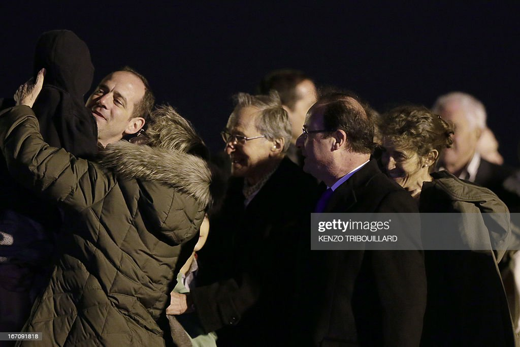 French President Francois Hollande (C) welcomes members of the Moulin-Fournier family as they arrive from Yaounde, at the Orly airport, near Paris, on April 20, 2013. A family of seven including four children who were held for two months by Islamists in Nigeria flew into Paris early Saturday days after having been released. French President Francois Hollande was waiting to welcome the Moulin-Fournier family at Orly airport just south of Paris, as they flew in from Cameroon, where they were freed late on April 18.