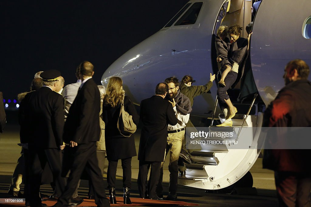 French President Francois Hollande (C) welcomes members of the Moulin-Fournier family arriving from Yaounde, at the Orly airport, near Paris, on April 20, 2013. A family of seven including four children who were held for two months by Islamists in Nigeria flew into Paris early Saturday days after having been released. French President Francois Hollande was waiting to welcome the Moulin-Fournier family at Orly airport just south of Paris, as they flew in from Cameroon, where they were freed late on April 18.