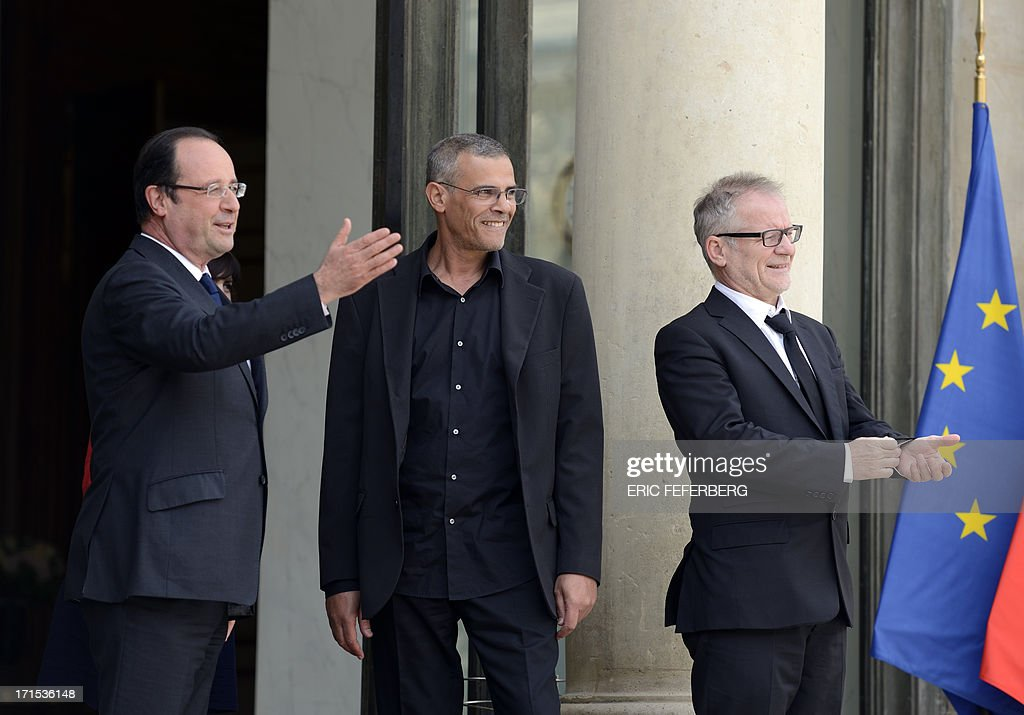 French President Francois Hollande (L) welcomes on June 26, 2013 French-Tunisian director Abdellatif Kechiche (C), the general delegate of the Cannes Film Festival Thierry Fremaux (R) and the actresses of the film for a lunch with the winners of the 2013 Palme d'Or at the Elysee Presidential palace in Paris. AFP PHOTO / ERIC FEFERBERG