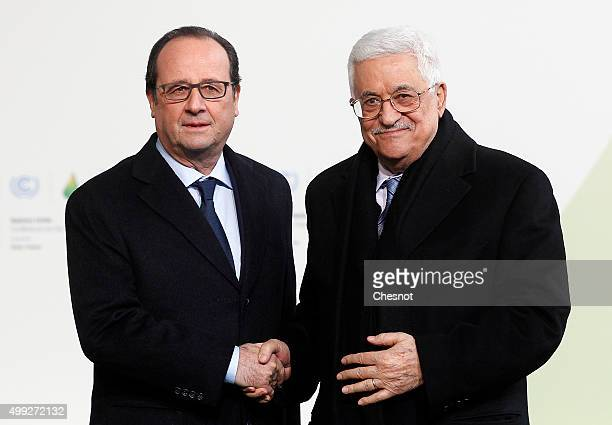 French President Francois Hollande welcomes Palestinian President Mahmoud Abbas as he arrives for the COP21 United Nations Climate Change Conference...