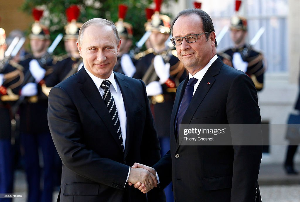French President Francois Hollande welcomes Russian President Vladimir Putin prior to their meeting at the Elysee Presidential Palace on October 02...