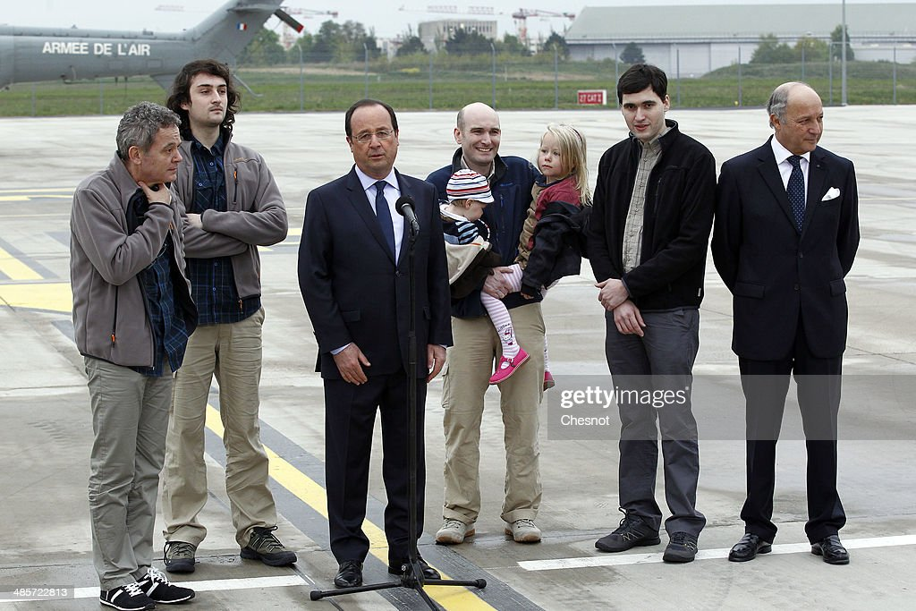 French President Francois Hollande with foreign minister Laurent Fabius flanked by the four French journalists Didier Francois Edouard Elias Nicolas...