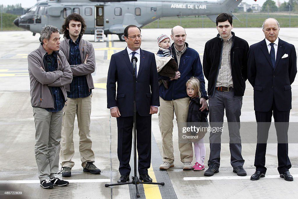 French President Francois Hollande, with foreign minister, <a gi-track='captionPersonalityLinkClicked' href=/galleries/search?phrase=Laurent+Fabius&family=editorial&specificpeople=540660 ng-click='$event.stopPropagation()'>Laurent Fabius</a>, flanked by the four French journalists, (L-R), <a gi-track='captionPersonalityLinkClicked' href=/galleries/search?phrase=Didier+Francois&family=editorial&specificpeople=4081314 ng-click='$event.stopPropagation()'>Didier Francois</a>, <a gi-track='captionPersonalityLinkClicked' href=/galleries/search?phrase=Edouard+Elias&family=editorial&specificpeople=11111806 ng-click='$event.stopPropagation()'>Edouard Elias</a>, <a gi-track='captionPersonalityLinkClicked' href=/galleries/search?phrase=Nicolas+Henin&family=editorial&specificpeople=11458605 ng-click='$event.stopPropagation()'>Nicolas Henin</a>, <a gi-track='captionPersonalityLinkClicked' href=/galleries/search?phrase=Pierre+Torres&family=editorial&specificpeople=9605453 ng-click='$event.stopPropagation()'>Pierre Torres</a> taken hostage in Syria, speaks to the press upon their arrival at the Villacoublay military airport on April 20, 2014 in Velizy-Villacoublay, France. The four French journalists taken hostage in Syria last year were freed after a 10-month captivity in the world's most dangerous country for the media.