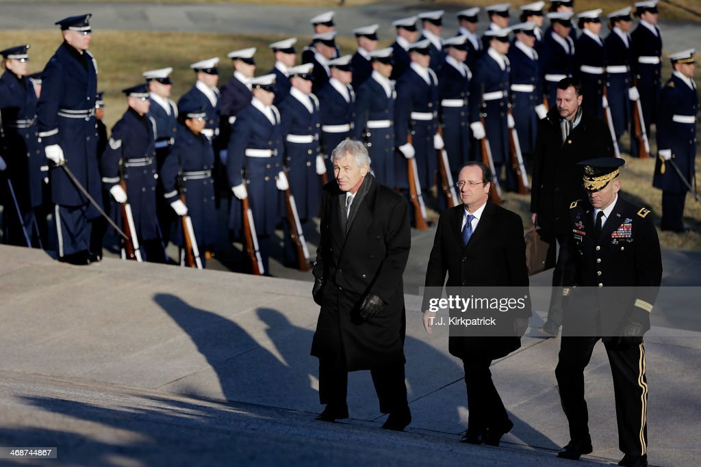 French President Francois Hollande (C), with U.S. Secretary of Defense <a gi-track='captionPersonalityLinkClicked' href=/galleries/search?phrase=Chuck+Hagel&family=editorial&specificpeople=504963 ng-click='$event.stopPropagation()'>Chuck Hagel</a> (L) and Maj. Gen. Jeffrey S. Buchanan, commander of the U.S. Army Military District of Washington, walk past an honor guard in a procession to the Tomb of the Unknown Soldier at Arlington National Cemetery on February 11, 2014 in Arlington, Virginia. 2014 marks the 70th anniversary of the Allied Forces D-Day landing in Normandy, which helped lead to the liberation of France and the European continent.