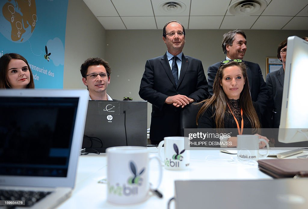 French president François Hollande (C) and mayor of Grenoble Michel Destot (R) meet with employees of Wizbii start-up on January 23, 2013 in Grenoble, French Alps.