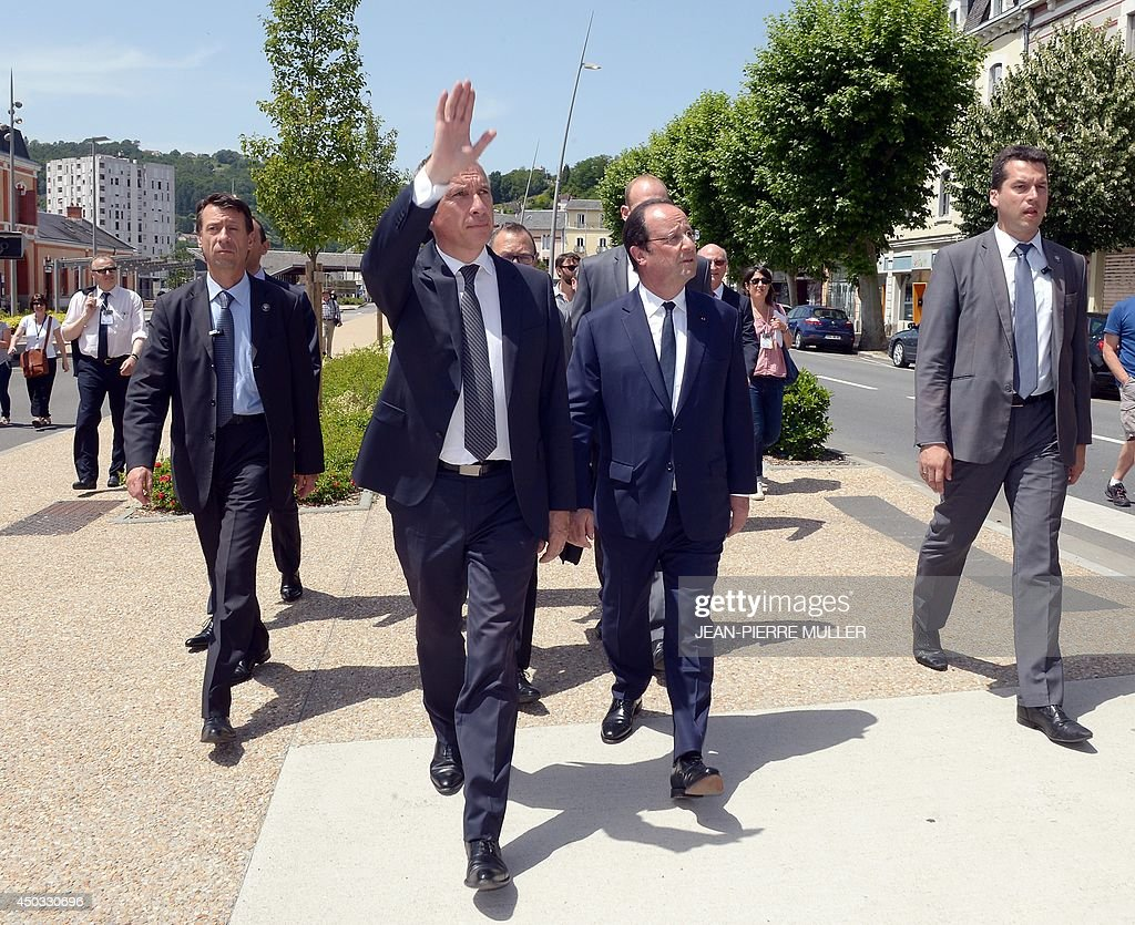 French President François Hollande (C) and Tulle Mayor Bernard Combes (L) walk in a street on June 9, 2014 in Tulle, southwestern France, before taking part in a ceremony in tribute to the memory of Nazi victims in Tulle. On June 9, 1944, 99 hostages were hanged from lampposts and balconies by the SS Division Das Reich in Tulle. AFP PHOTO / JEAN-PIERRE MULLER