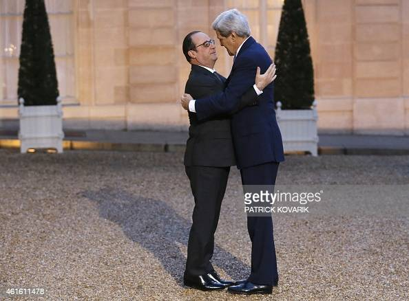 French president François Hollande embraces US Secretary of State John Kerry prior to a meeting at the Elysee Palace on January 16 2015 in Paris...