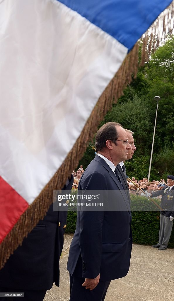 French President François Hollande (foreground), flanked by Tulle Mayor Bernard Combes, observes a minute of silence in front of the stele to the memory of Nazi victims during a souvenir ceremony, on June 9, 2014 in Tulle, southwestern France. 99 hostages were hanged from lampposts and balconies by the SS Division Das Reich in Tulle, on June 9, 1944, during the WWII.