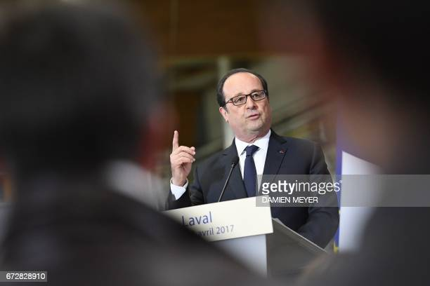French President François Hollande gestures as delivers a speech during a visit at a textile company in Laval on April 25 2017 / AFP PHOTO / DAMIEN...