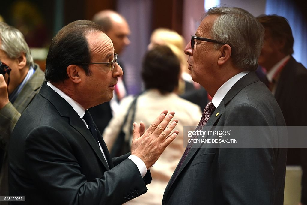 French President François Hollande (L) gestures as he talks with the European Commission President Jean Claude Juncker (R) during EU - Summit at the EU headquarters in Brussels on June 28, 2016. Prime Minister David Cameron said today he wants the 'closest possible' relations with the EU after Britain voted to leave the bloc, adding the split should be 'as constructive as possible'. As he arrived at a Brussels summit, Cameron, who is to step down within weeks, told reporters that, while Britain was leaving the EU, 'we mustn't be turning our backs on Europe.' SAKUTIN