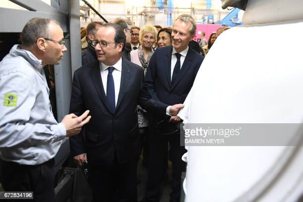 French President François Hollande listens to an employee as he visits a textile company in Laval on April 25 2017 / AFP PHOTO / DAMIEN MEYER