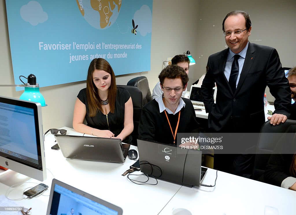 French President François Hollande (R) meet with employees of Wizbii start-up on January 23, 2013 in Grenoble, French Alps, during a visit in this town for a New Year wishes ceremony for Youth. The board reads 'To favorize jobs and Entrepreneurship of Youth around the world'.