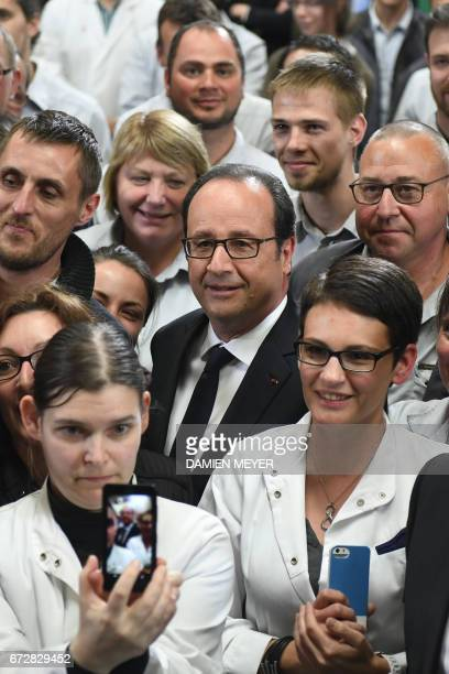French President François Hollande meets employees as he visits a textile company in Laval on April 25 2017 / AFP PHOTO / DAMIEN MEYER