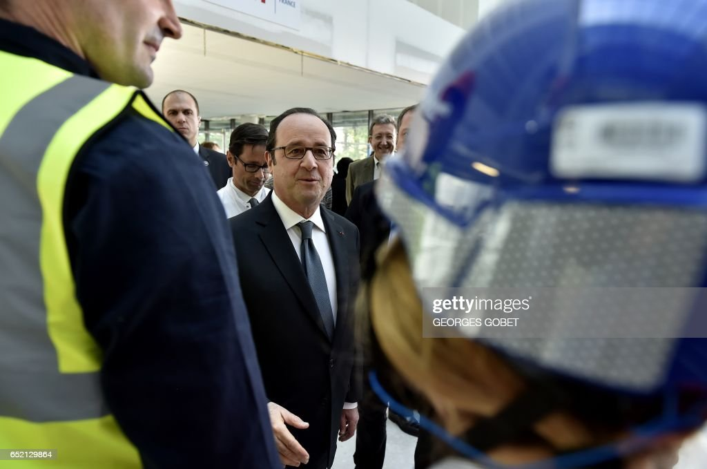 French president François Hollande (L) shakes hands with a worker as he visits the works of the future Robert Boulin hospital on March 11, 2017 in Libourne, southwestern France. /