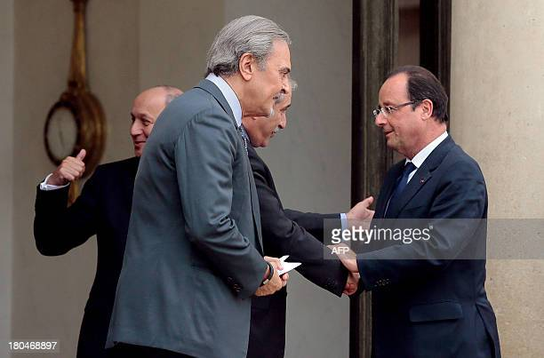 French president François Hollande shakes hands with Jordanian Foreign minister Nasser Judeh eyed by Saudi Foreign Minister Saud alFaisal after their...