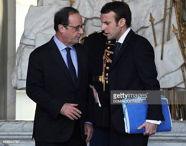 French President François Hollande speaks with French Economy and Industry minister Emmanuel Macron in the Elysee Palace after the weekly Council of...