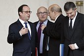 French President François Hollande speaks with French Finance Minister Michel Sapin French Defence Minister JeanYves Le Drian and French presidential...