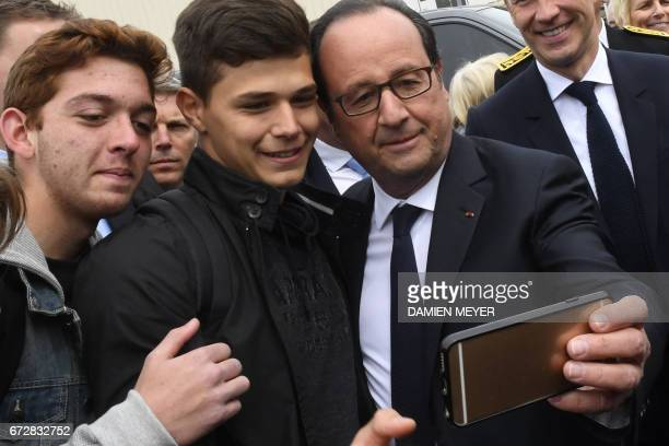 French President François Hollande takes selfie pictures before visiting a textile company in Laval on April 25 2017 / AFP PHOTO / DAMIEN MEYER