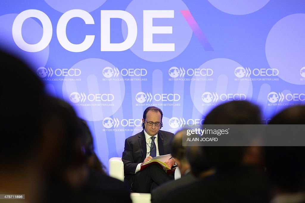 French President François Hollande writes notes prior to delivering remarks on 'Investment and Climate' during the OECD Ministerial Council meeting...