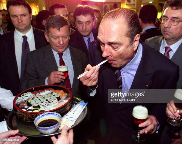 French President Jacques Chirac and Agriculture Minister Jean Glavany eat some sushis 18 February 2001 after opening France's annual Agricultural...