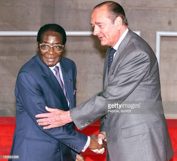 French President Jacques Chirac greets his Zimbabwean counterpart Robert Mugabe at the opening of the 20th FrancoAfrican summit in Paris 27 November...