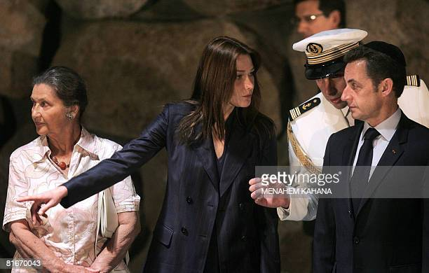 French President Nicolas Sarkozy accompanied by his wife Carla BruniSarkozy and French philosopher and Holocaust survivor Simone Weil stand during a...