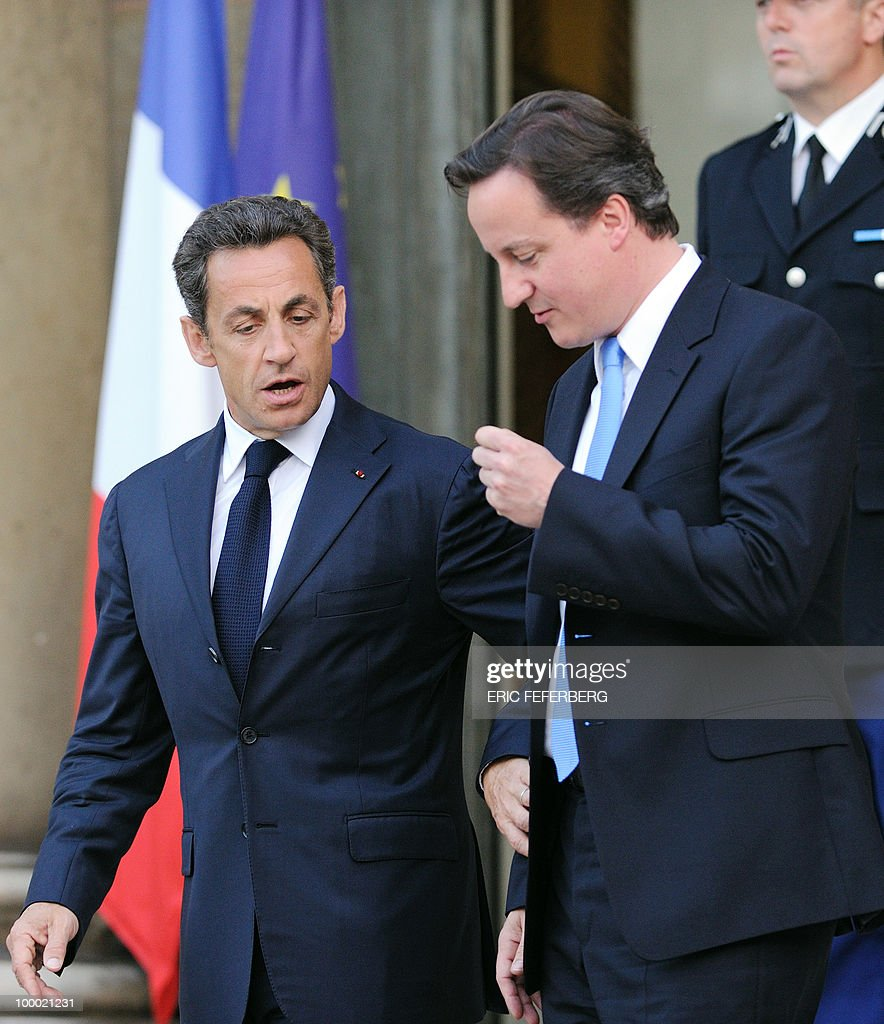French President Nicolas Sarkozy (L) accompanies the new Britain's Prime minister David Cameron after their diner at the Elysee Palace on May 20, 2010 in Paris. Cameron and his coalition deputy unveiled full details today of their 'historic' power-sharing deal, under growing scrutiny for signs of strain.
