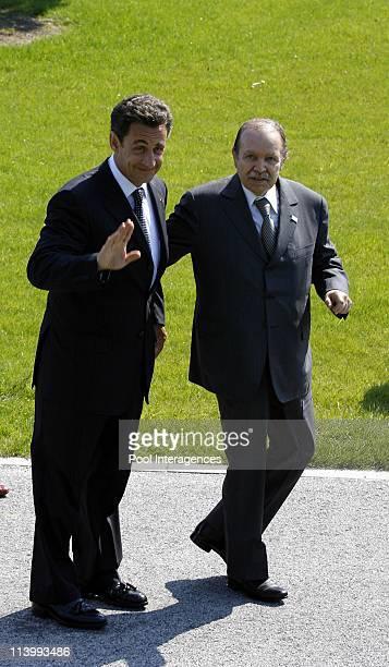 French President Nicolas Sarkozy and Algerian President Abdelaziz Bouteflika walk together to reach the G8 and outreach countries family photo In...