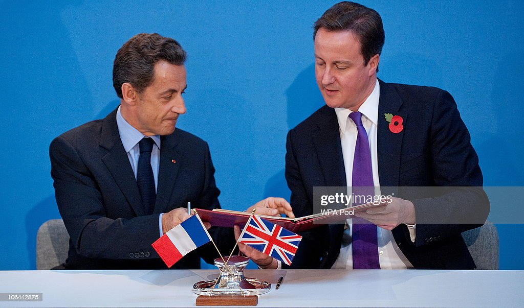 French President Nicolas Sarkozy and British Prime Minister David Cameron exchange copies after signing a treaty during an AngloFrench summit at...