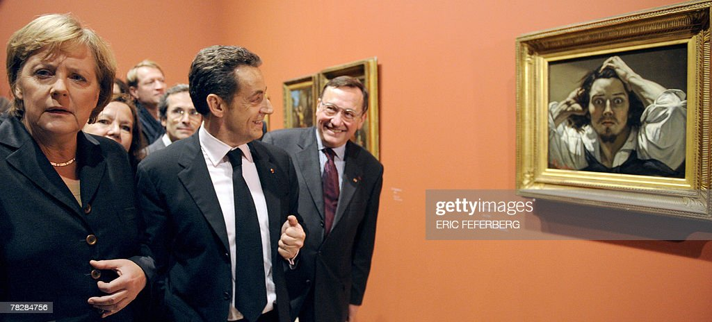 French president Nicolas Sarkozy and German Chancellor Angela Merkel look at a selfportrait by Gustave Courbet during a visit to the French artist...