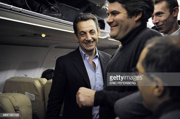 French President Nicolas Sarkozy and his communication adviser Franck Louvrier are seen in the plane that will bring Sarkozy to Kabul 21 December...