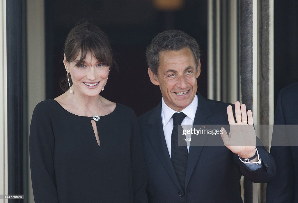 French President <a gi-track='captionPersonalityLinkClicked' href=/galleries/search?phrase=Nicolas+Sarkozy&family=editorial&specificpeople=211375 ng-click='$event.stopPropagation()'>Nicolas Sarkozy</a> and his pregnant wife <a gi-track='captionPersonalityLinkClicked' href=/galleries/search?phrase=Carla+Bruni&family=editorial&specificpeople=235729 ng-click='$event.stopPropagation()'>Carla Bruni</a>-Sarkozy await the arrival of G8 member state leaders and their spouses for an evening dinner function at Le Ciro's Restaurant at the G8 Summit on May 26, 2011 in Deauville, France. Heads of the world's wealthiest nations are meeting in Deauville, France, for the G8 summit to discuss various security, aid and trade issues, including the 'Arab Spring', nuclear safety and climate change.