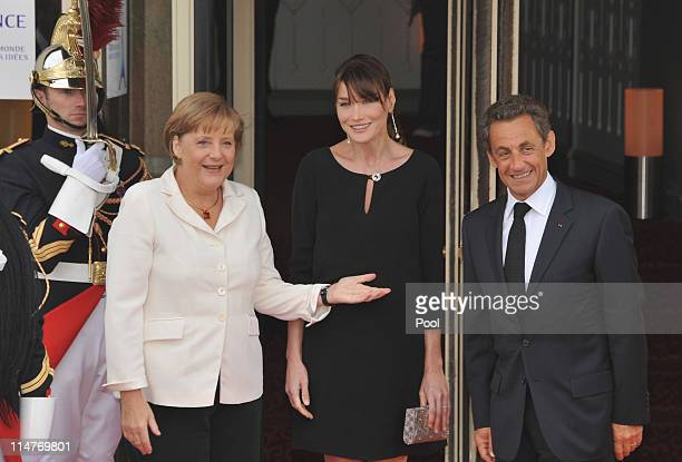 French President Nicolas Sarkozy and his pregnant wife Carla BruniSarkozy greet German Chancellor Angela Merkel upon their arrival at Le Ciro's...