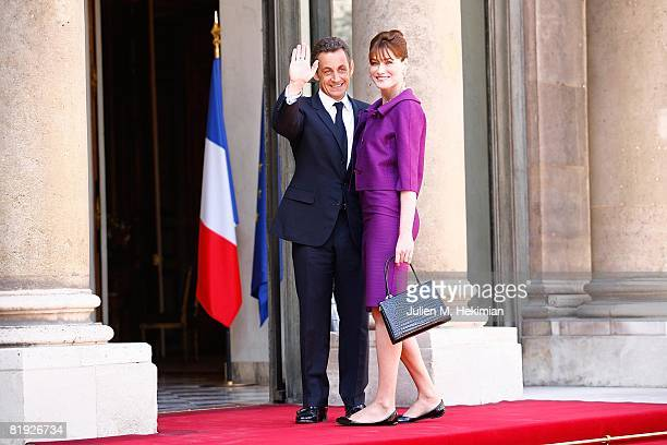 French President Nicolas Sarkozy and his wife Carla BruniSarkozy arrive in the courtyard of the Elysee for the garden party following the Bastille...
