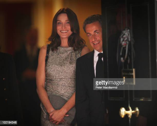 French President Nicolas Sarkozy and his wife Carla BruniSarkozy look out from behind the door at Number 10 Downing after lunching with Prime...