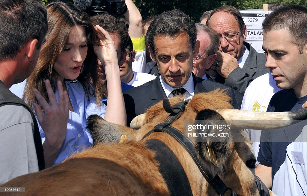 French President Nicolas Sarkozy (C) and his wife Carla Bruni-Sarkozy (2nd L) speak with cow breeders as they visit exhibitions on the Champs-Elysees in Paris, on May 24, 2010. The young French farmers' union organized a two-day event called 'Nature Capitale' where they installed the fields and forest of France in the French capital. The union, representing farmers under the age of 35, aim to showcase farm production from sheep breeding to crop growing and win public support for their embattled sector.