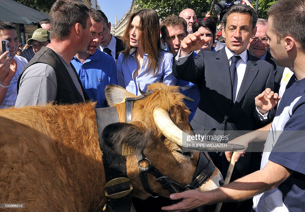 French President Nicolas Sarkozy (2nd R) and his wife Carla Bruni-Sarkozy (C) speak with cow breeders as they visit exhibitions on the Champs-Elysees in Paris, on May 24, 2010. The young French farmers' union organized a two-day event called 'Nature Capitale' where they installed the fields and forest of France in the French capital. The union, representing farmers under the age of 35, aim to showcase farm production from sheep breeding to crop growing and win public support for their embattled sector.