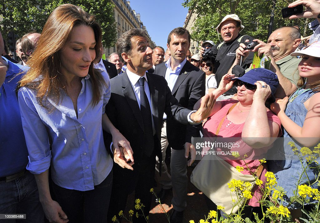 French President Nicolas Sarkozy (2ndR) and his wife Carla Bruni-Sarkozy (R) walk among the crowd as they visit exhibitions on the Champs-Elysees in Paris, on May 24, 2010. The young French farmers' union organized a two-day event called 'Nature Capitale' where they installed the fields and forest of France in the French capital. The union, representing farmers under the age of 35, aim to showcase farm production from sheep breeding to crop growing and win public support for their embattled sector.